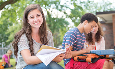 Smiling young lady reviewing her notebook on a bench outside at her school.