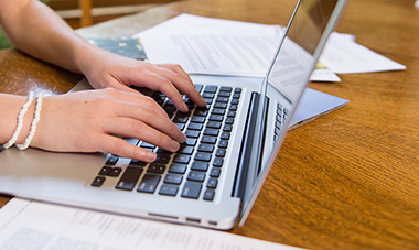 Close-up of an individual's hands typing on a laptop.