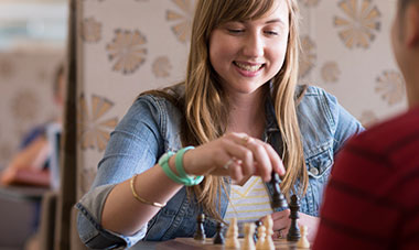 Close-up of cheerful young lady playing chess with her opponent.