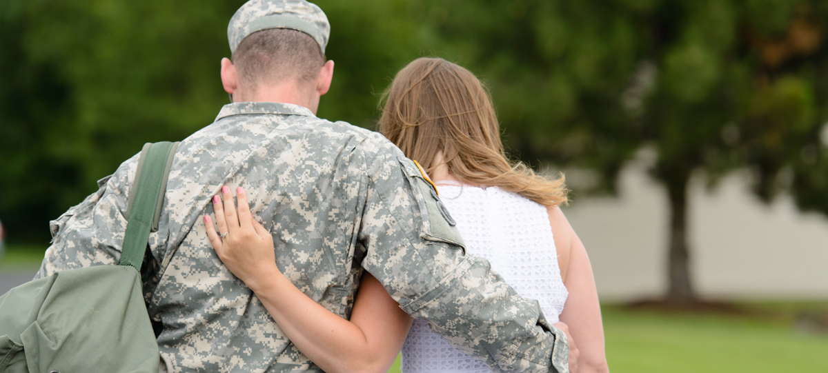 "Close-up of a servicemember and his wife, walking hand in hand. A sign advising ""Free Help. Don't pay a fee for student loan services."" is near the photo."