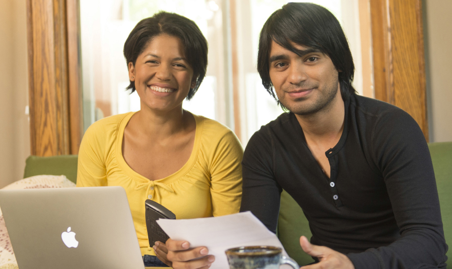 Smiling man and woman working together on their computer at home.